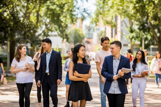 A group of students carrying laptops and notepads whilst travelling down the UNSW walkway