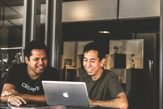 two unsw male students smiling at laptop