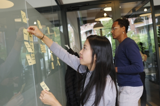 A female UNSW Management student sticking post-it notes on a wall