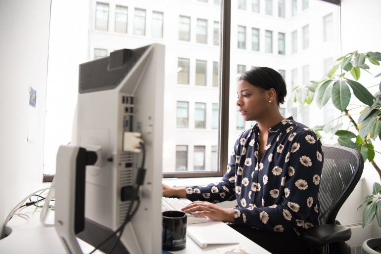 corporate woman sitting in front of computer screens