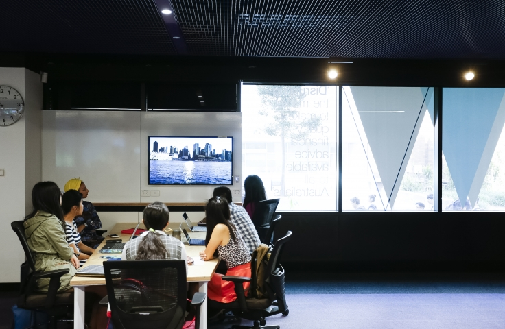 A group of students sitting at a desk, watching a presentation on a screen in The Place