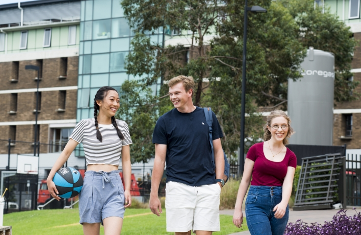 Three undergraduate students walking around the UNSW sports oval