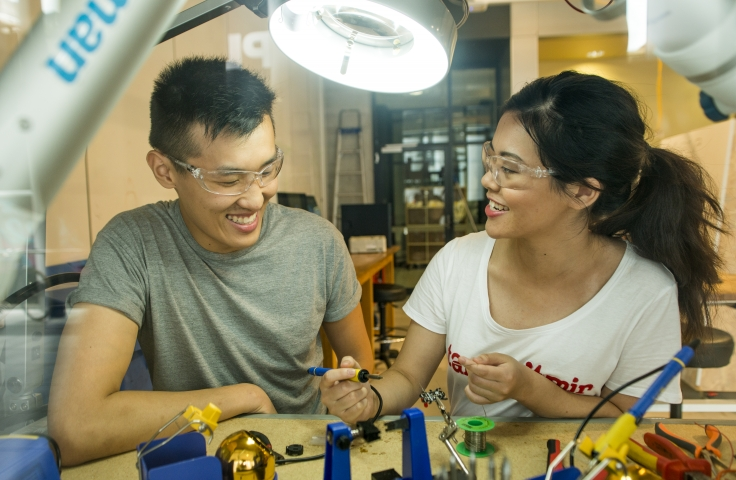 Two students wearing safety goggles in a lab