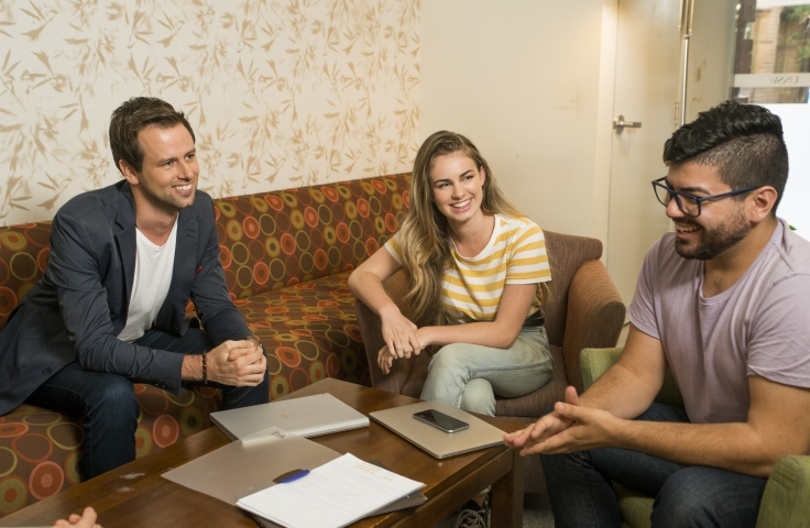 Two students sitting with a student advisor on a couch