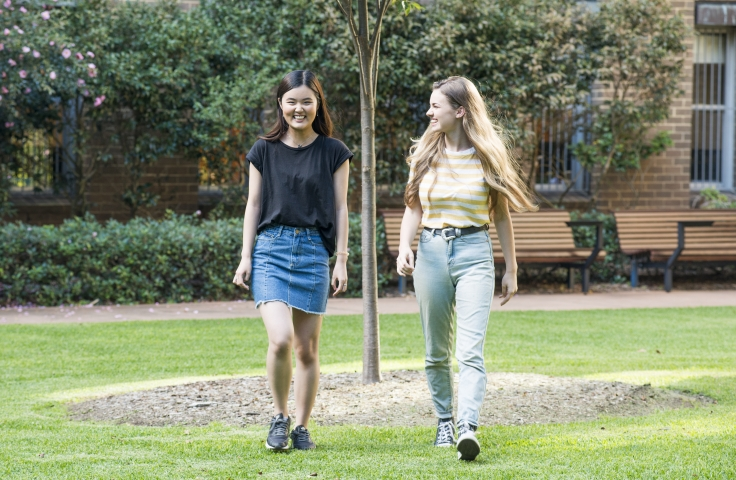 Two female students walking together on campus