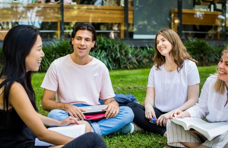 Four students sitting cross-legged on the grass on the Kensington campus