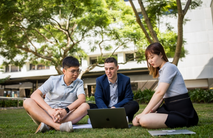 three accounting students sitting on the grass looking at laptop