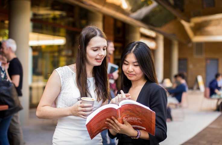 two actuarial research students standing in front of unsw bookshop reading a text book