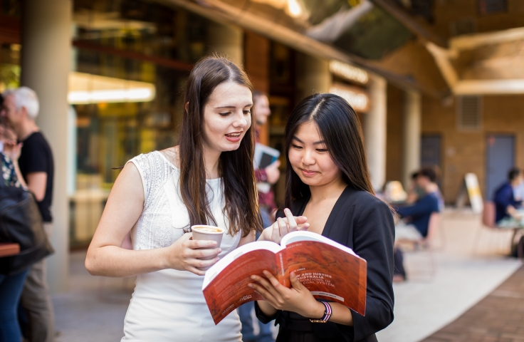 two students reading banking book in front of unsw cafe