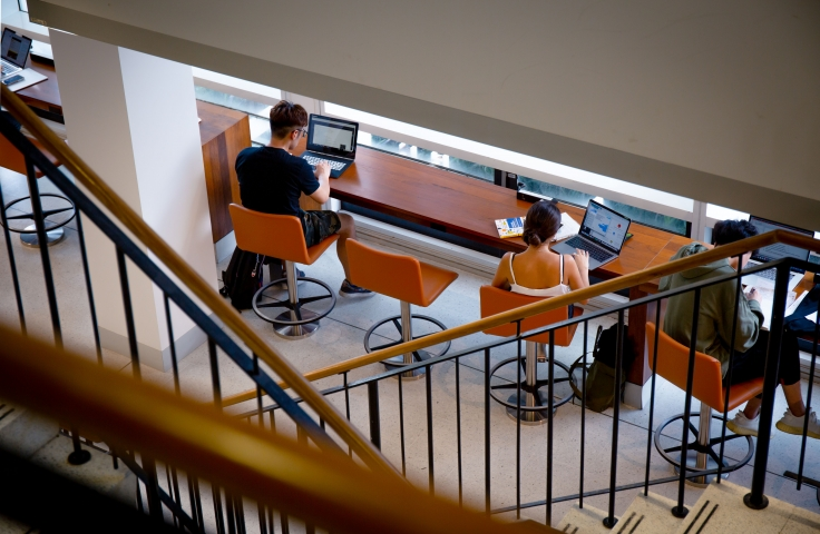 Students sitting on orange stools in the Business School building