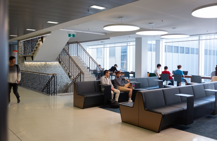 Students sitting at communal couches in the Business School building
