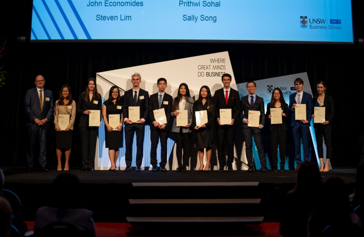 Students lined up on the podium with their certificates at the UNSW Business Award Ceremony