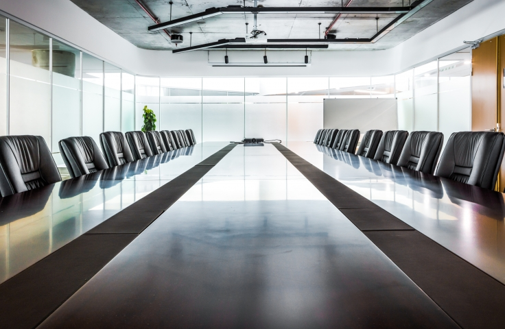 Large boardroom table surrounded by chairs
