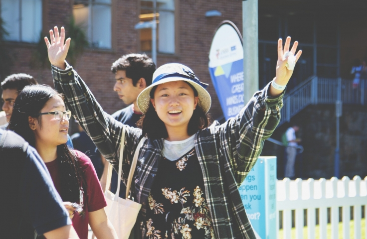 unsw student smiling with arms in the air on open day