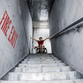 Evianne Grosvenor sits in her wheelchair at the top of a flight of steps labelled Fire Escape