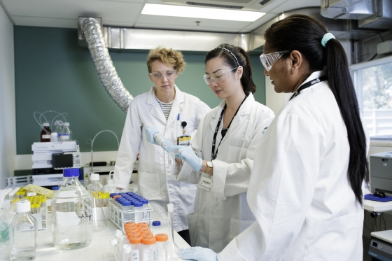 Three female postgraduate research students wearing white coats in a lab