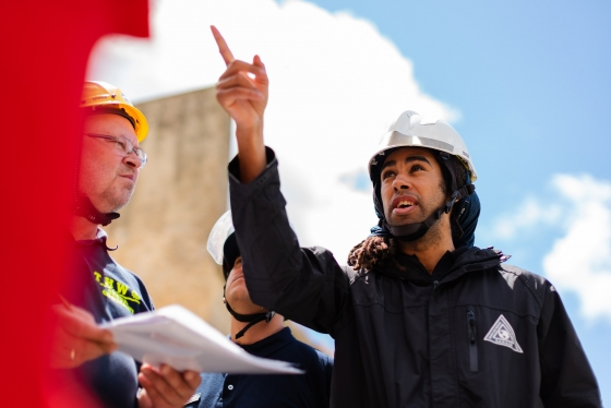 Civil Engineer researcher in a hard hat, speaking with two colleagues