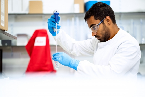 Male in a white lab coat using equipment in a laboratory