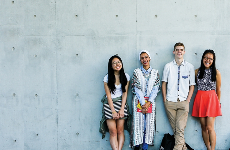 Four undergraduate students leaning against a wall on campus